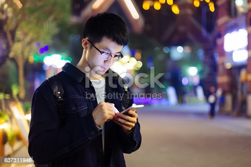 istock young asian man hold mobile phone on street at night 637311946