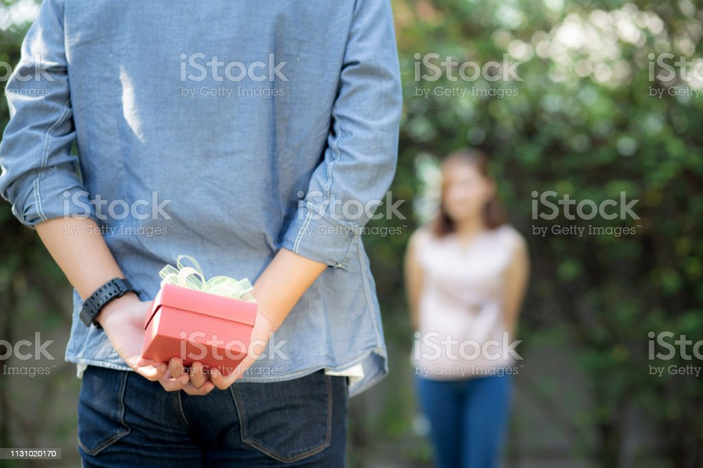 Young asian man holding behind back gift box surprise girlfriend...