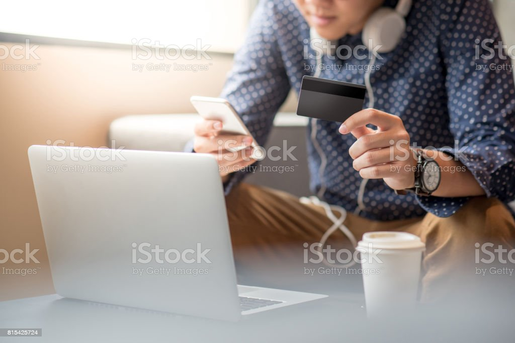 Young Asian man holding credit card and using smartphone for online shopping stock photo