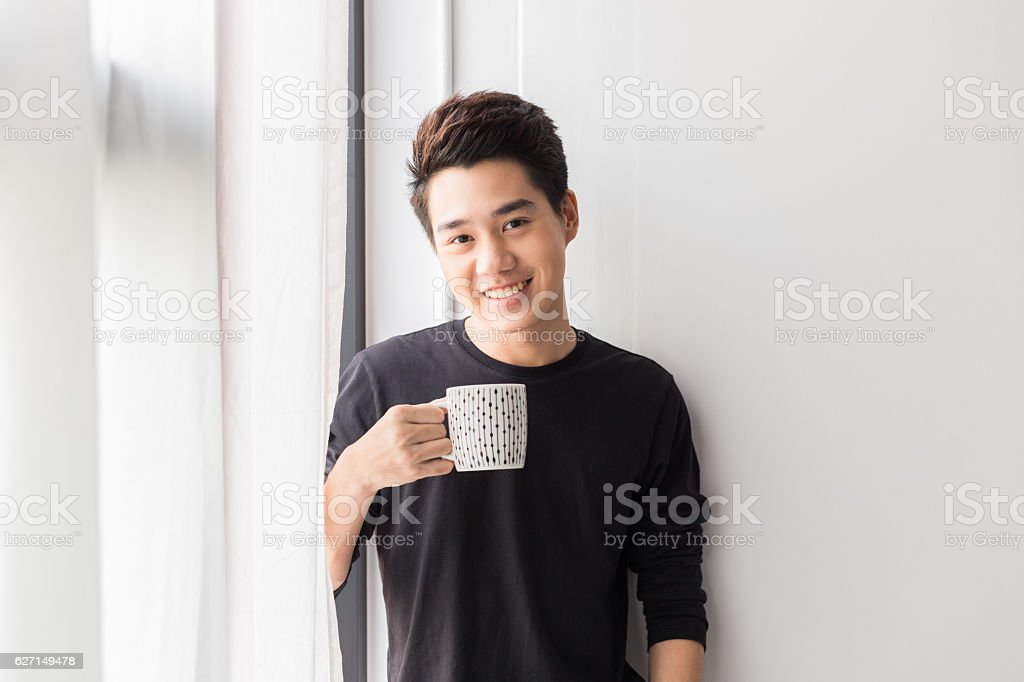Young Asian Man holding cup stock photo