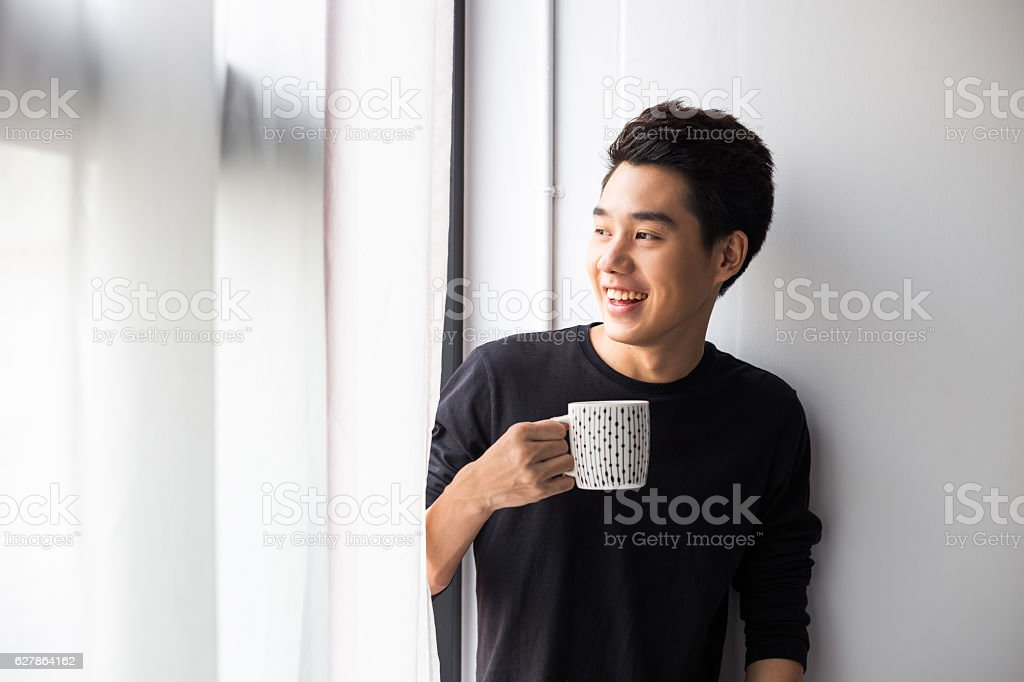 Young Asian Man holding mug stock photo