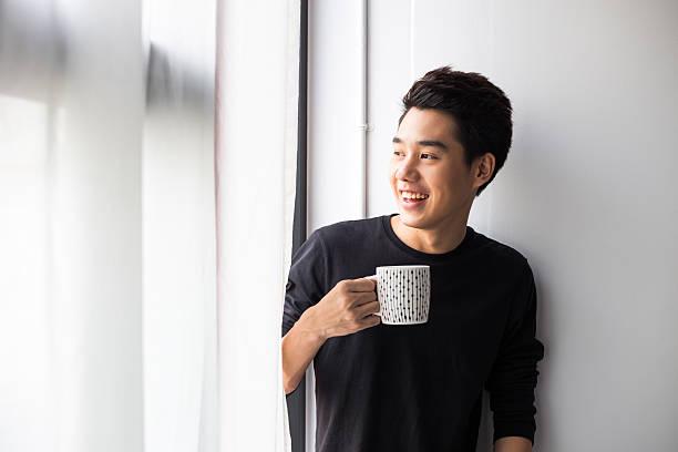 Young Asian Man holding mug stock photo
