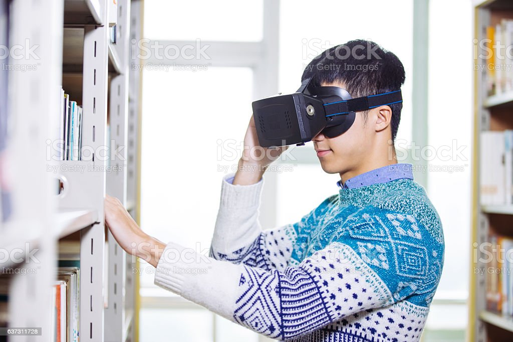young asian man holds VR in library - foto de acervo