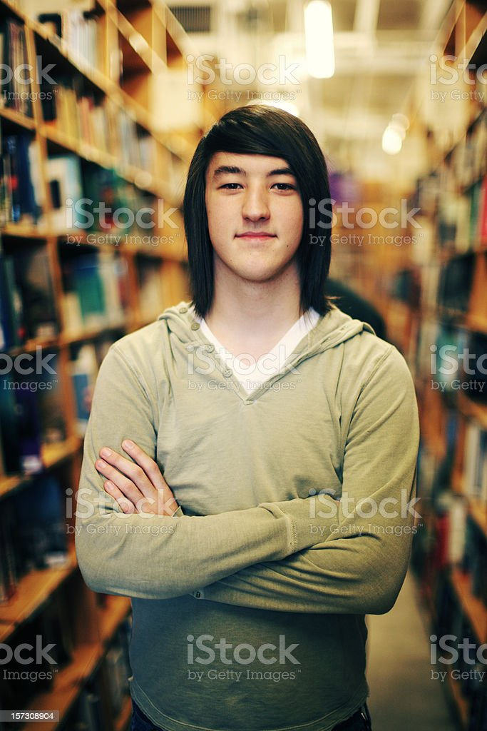 Young Asian Man in a Bookstore Aisle royalty-free stock photo