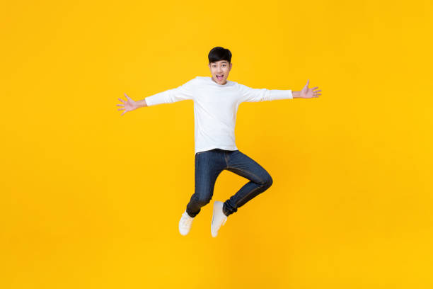 Young Asian man in casual clothes jumping stock photo