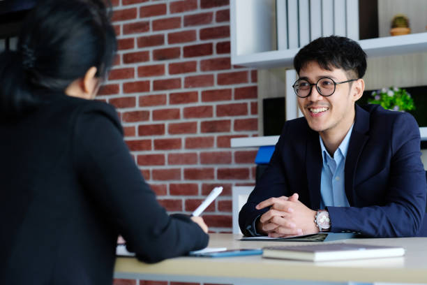 Young asian man in job interview with businesswoman at office background, job search, business concept stock photo