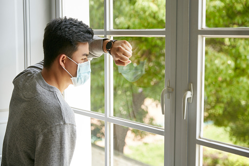 young asian man leaning against window looking at trees outside