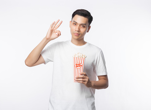 Young asian man in white t-shirt holding popcorn and makes okay gesture isolated on white background
