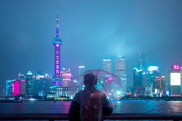 Young Asian man is smiling and using smart phone while staying at Shanghai landmark view at the background while raining.