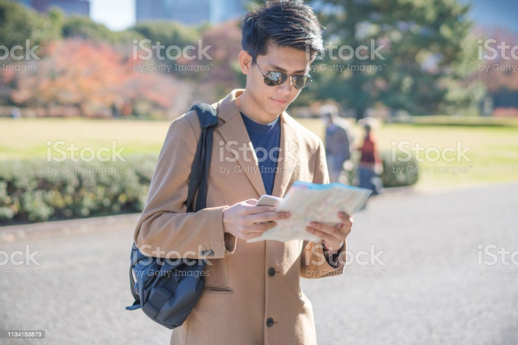 Young asian man japanese looking for travel location using mobile...