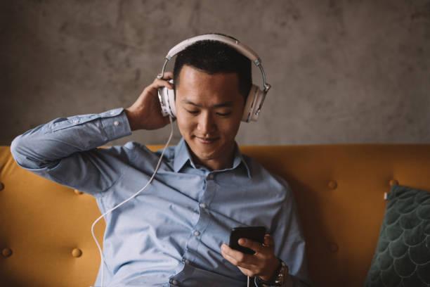 年輕的亞洲人聽音樂, 在他的辦公室放鬆 - music 個照片及圖片檔