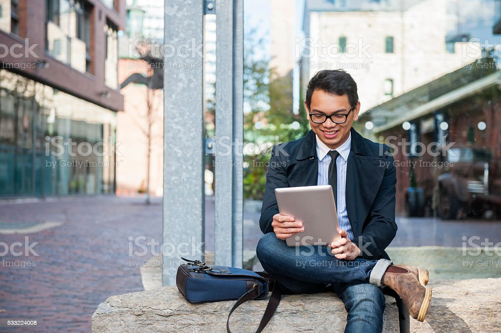 Young asian man looking at digital tablet stock photo