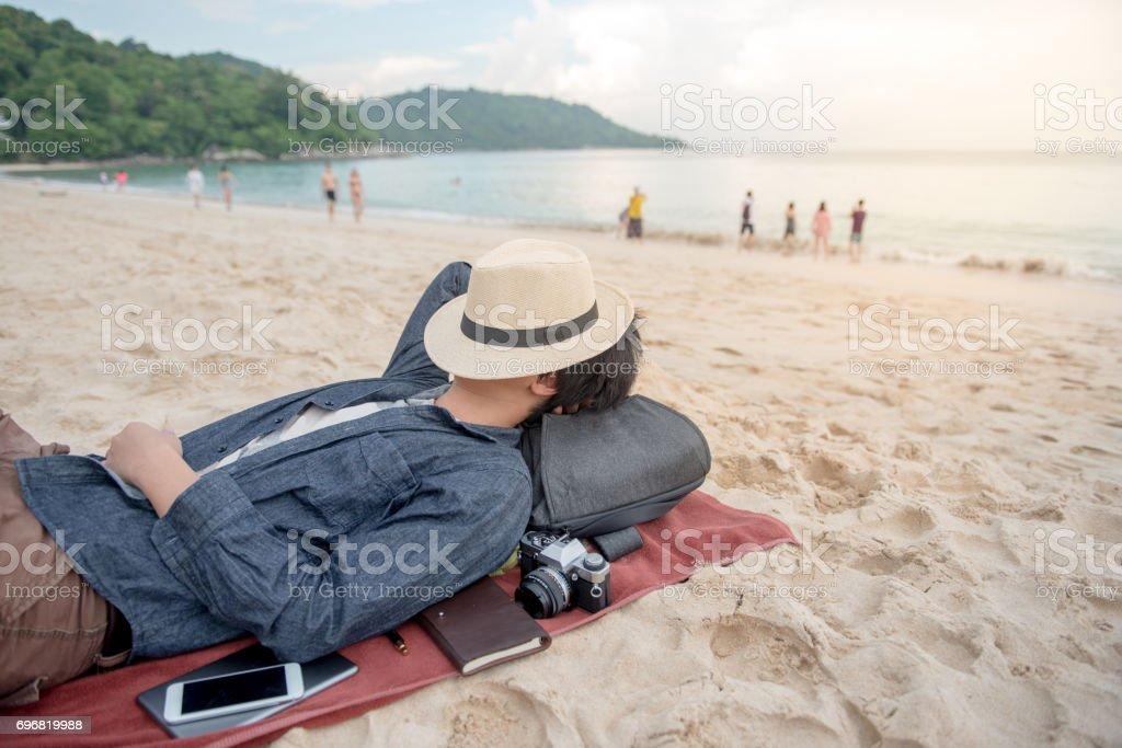 jovem asiático homem deitado na praia e fechar a cara de chapéu - foto de acervo