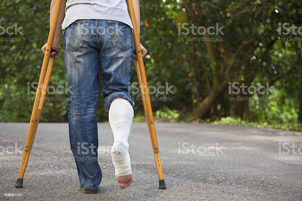 Young asian man on crutches with tree background stock photo