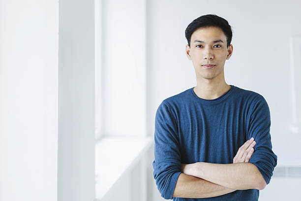 Young Asian Man Portrait of young asian man, looking at camera, confident. japanese ethnicity stock pictures, royalty-free photos & images