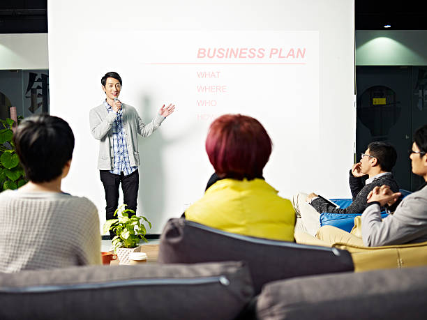 young asian man presenting business plan - 発表 ストックフォトと画像