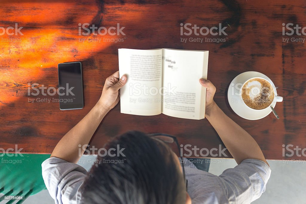 Young Asian man reading book with smartphone and coffee beside
