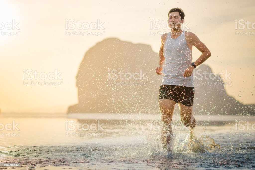 Young asian man running on beach with sunset in background foto stock royalty-free