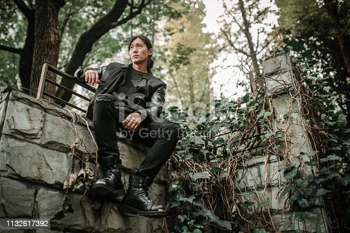 Handsome Asian man with long hair and black outfit sitting on concrete wall