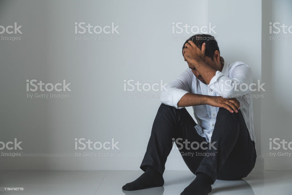 Young asian man sitting in the dark room hand in head feeling...