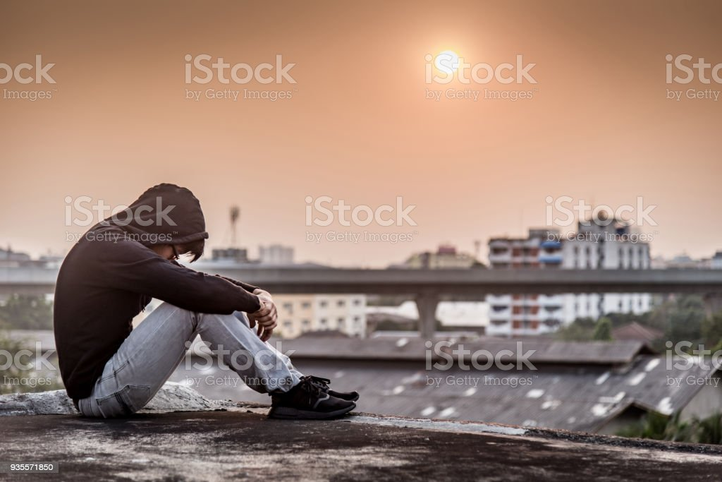 Young Asian man sitting on rooftop of abandoned building with depression stress out during sunset time in the city stock photo