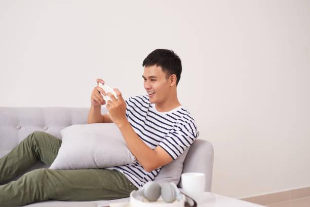 junge asiatische mann auf sofa sitzen und spielen auf handy zu hause - free online game stock-fotos und bilder