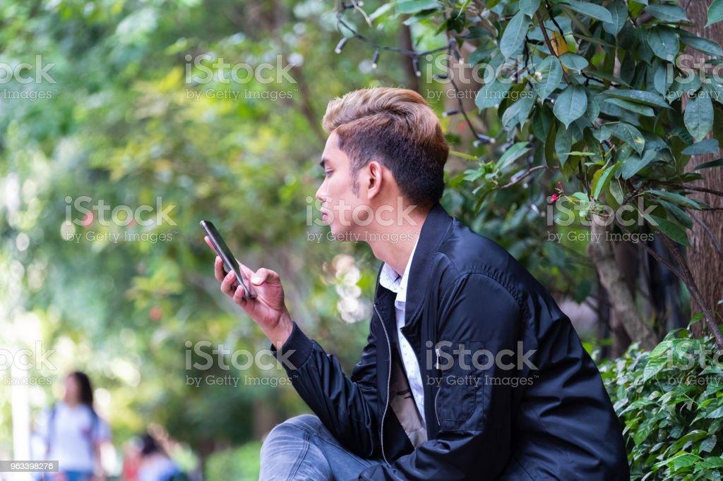 Young asian man sitting on the sidewalk using his mobile phone - Zbiór zdjęć royalty-free (25-29 lat)