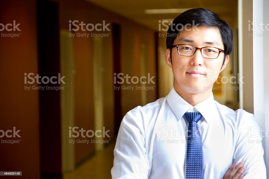 Young Asian Man Standing in the Corridor by the Window stock photo