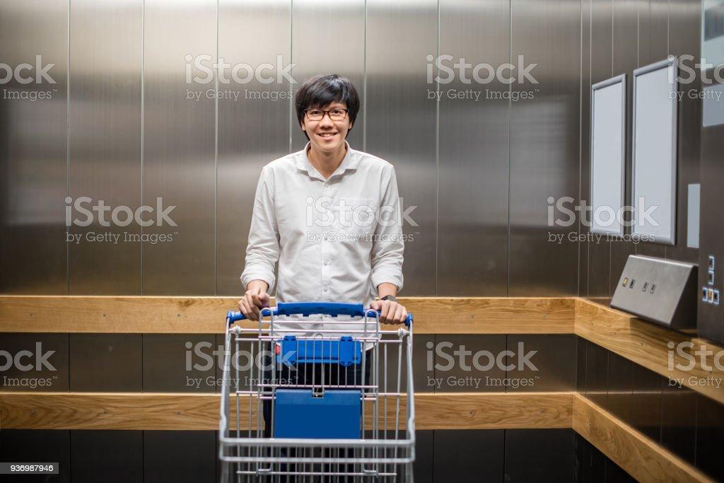 951e8b6b01 Jovem asiático com carrinho carrinho vazio no elevador ou elevador de pé  foto de stock royalty