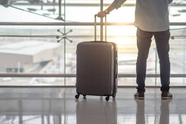 Young Asian man standing with suitcase luggage in the international airport terminal stock photo
