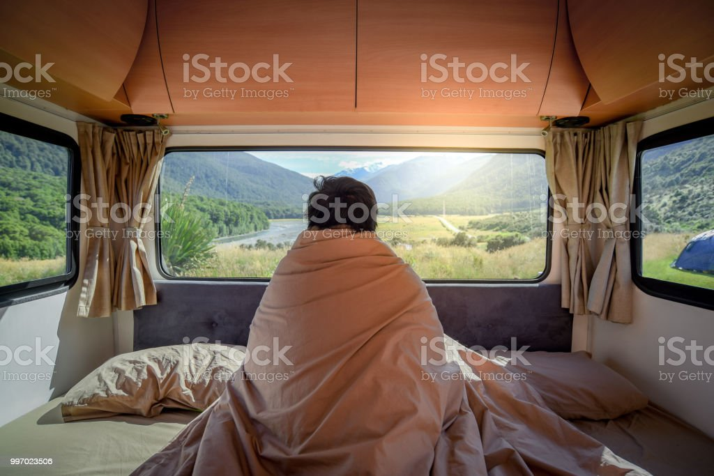 Young Asian man staying in the blanket looking at mountain scenery through the window in camper van in the morning. Road trip in summer of South Island, New Zealand. stock photo