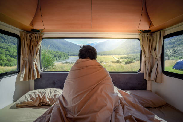 Young Asian man staying in the blanket looking at mountain scenery through the window in camper van in the morning. Road trip in summer of South Island, New Zealand. Young Asian man staying in the blanket looking at mountain scenery through the window in camper van in the morning. Road trip in summer of South Island, New Zealand. rv interior stock pictures, royalty-free photos & images