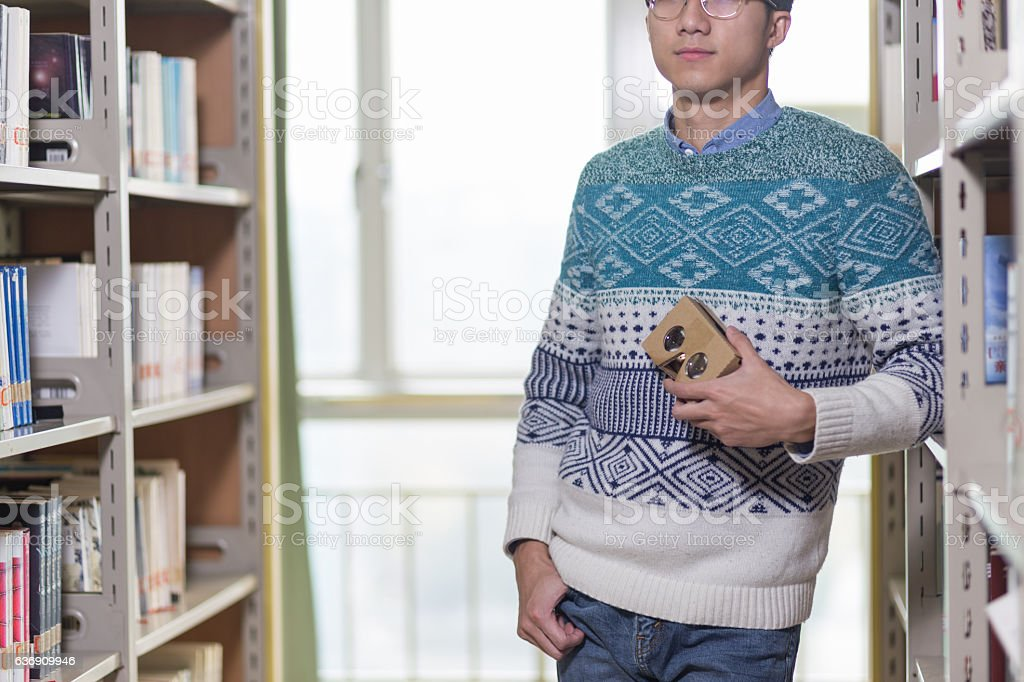 young asian man student holds VR in library - foto de acervo