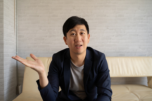 Young Asian man talking in video call with business colleagues at home. Businessman having online video conference discussion in suit