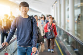 若いアジア人は公共交通機関で旅行し、空港で電車を待っています