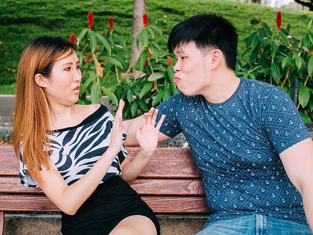 Young Asian man trying to kiss girl & get rejected Young Asian man trying to kiss a girl and gets rejected bad date stock pictures, royalty-free photos & images