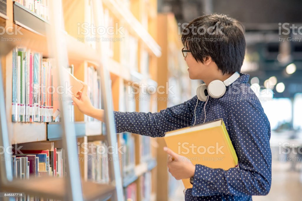 Young Asian man university student choosing book in library stock photo