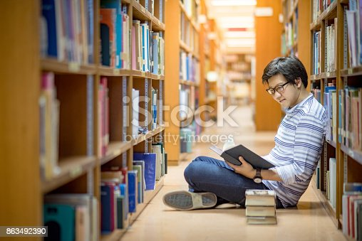istock Young Asian man university student reading book in library 863492390