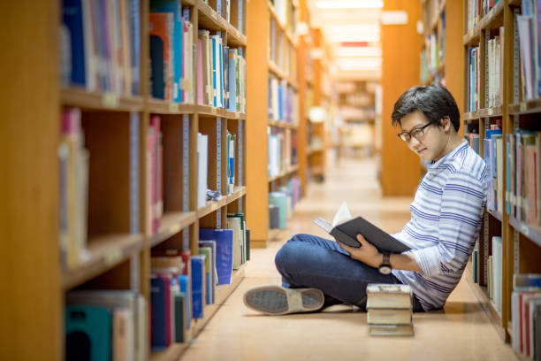 young asian man university student reading book in library - literature stock pictures, royalty-free photos & images