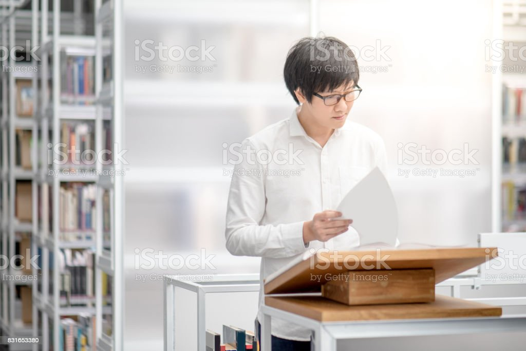 Young Asian man university student reading recommended book on podium in library stock photo