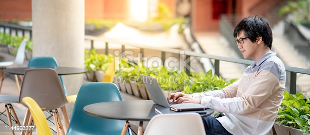 istock Young Asian man university student with glasses using laptop computer on the table in public area of college. Campus lifestyle in education building. Research and scholarship concepts 1144963277
