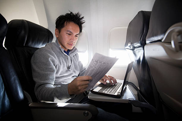 Young Asian man using laptop and reading newspaper on plane stock photo