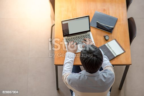 Young Asian man using laptop computer in the college from top view. university student lifestyle in education building.