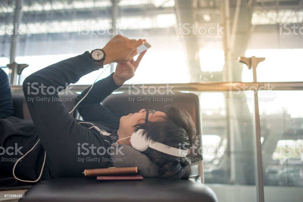 Young Asian man using smartphone and listening to music on bench in airport terminal stock photo
