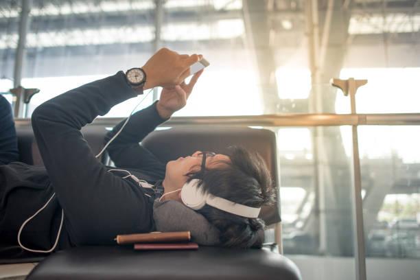 スマート フォンを使用して、空港のベンチで音楽を聞いて若いアジアの男 - ゲーム ヘッドフォン ストックフォトと画像