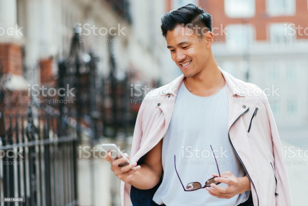 Young Asian man using smartphone for online messaging stock photo