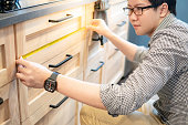 Young Asian man using tape measure for measuring drawer on wooden kitchen counter in showroom. Shopping furniture for home improvement. Interior design concept