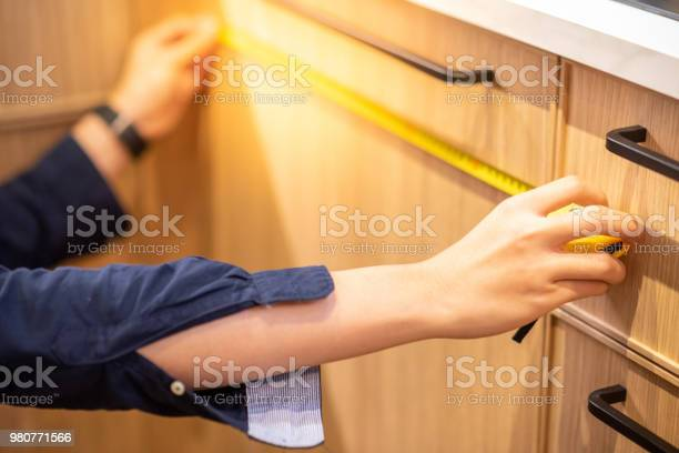 Young asian man using tape measure for measuring wooden kitchen in picture id980771566?b=1&k=6&m=980771566&s=612x612&h=sl7psx4n3jo1lskjdgkzcqw8anl87ux nr5wplubiis=