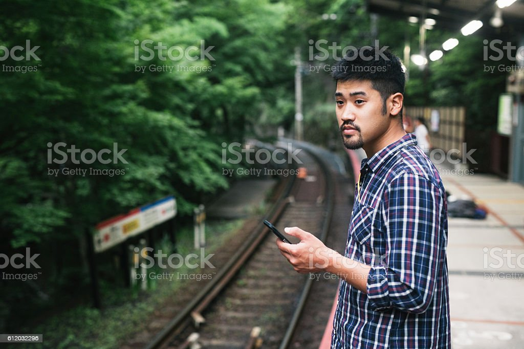 Young Asian Man Waitin for Train, Holding Phone stock photo