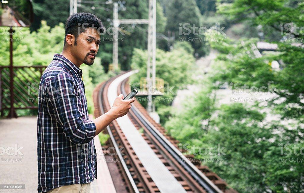 Young Asian Man Waitin for Train stock photo